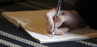 Mão de idoso escreve em caderno