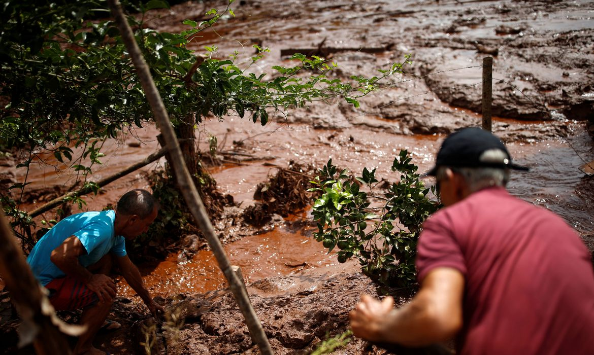 Residents work in a river covered by mud after a dam owned by Brazilian miner Vale SA that burst, in Brumadinho, Brazil January 26, 2019. REUTERS/Adriano Machado