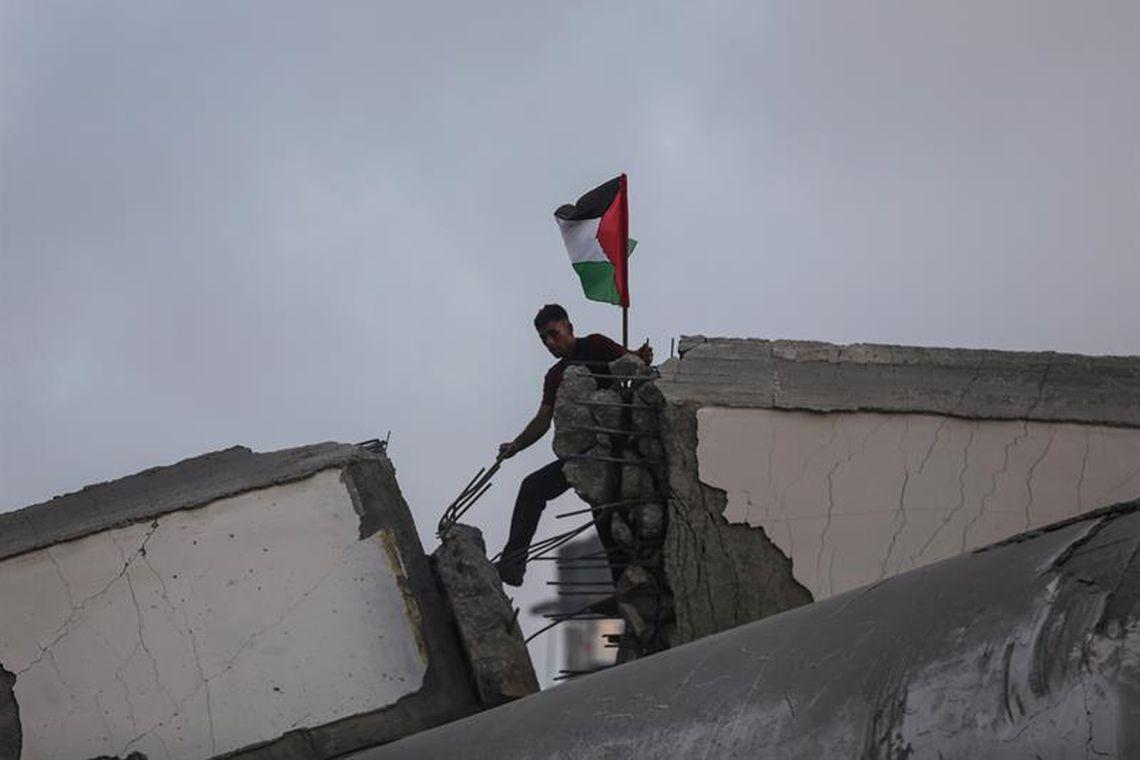 Grupo de palestinos inspeciona restos de um centro cultural destruído por un ataque aéreo israelense em Gaza