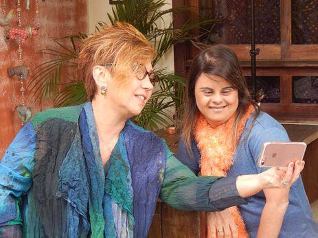 Descrição da foto:  Em área externa, Claudia e Fernanda estão lado a lado. Claudia segura seu celular rosa com uma das mãos esticadas, e Fernanda apoia um de seus cotovelos em um suporte de madeira. As duas olham para a tela do aparelho, sorridentes