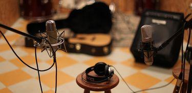 Pequeno estúdio com microfone e violão