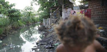 Imagem de riacho com falta de saneamento básico e uma criança passando em favela do Complexo da Maré