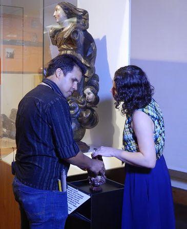 Descrição de foto: Na área interna do museu, Valéria está de frente para um homem, e os dois estão de perfil. Os dois estão tocando em uma reprodução tátil do acervo do museu.