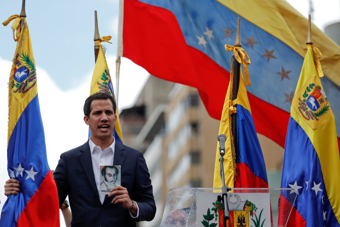 Juan Guaido, President of Venezuela's National Assembly, holds a copy of Venezuelan constitution during a rally against Venezuelan President Nicolas Maduro's government and to commemorate the 61st anniversary of the end of the dictatorship of