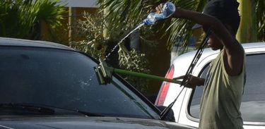Menino trabalha limpando carros no semáforo