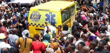 People gather around an ambulance at the site of a collapsed building containing a school in Nigeria's commercial capital of Lagos, Nigeria March 13, 2019. REUTERS/Temilade Adelaja