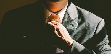 Detalhe de homem de terno ajustando a gravata