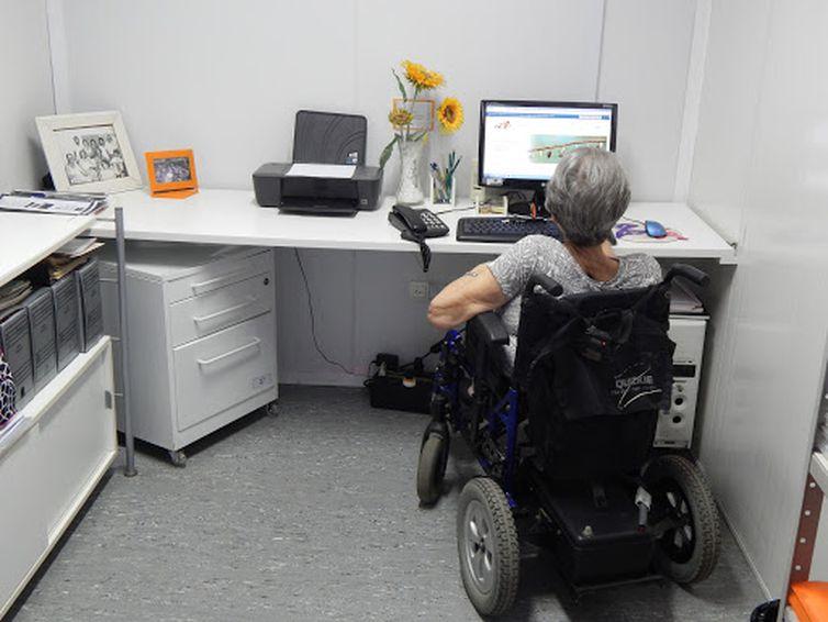 Em um escritório, a psicóloga Lilia Martins está sentada em uma cadeira de rodas motorizada, de costas para nós, e de frente para uma mesa com computador, telefone, impressora, portas-retratos e girassóis amarelos