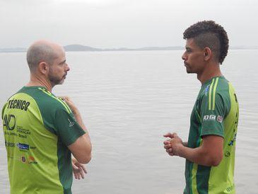 Descrição de foto: Com o mar ao fundo, Luiz Ricardo está ao lado de Eduardo Duarte. Os dois estão de frente um para o outro, de perfil, e vestem o mesmo uniforme verde.