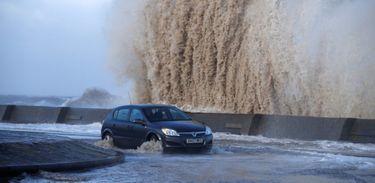 Carro passa por estrada alagada pela tempestade Eleanor em New Brighton, no Reino Unido