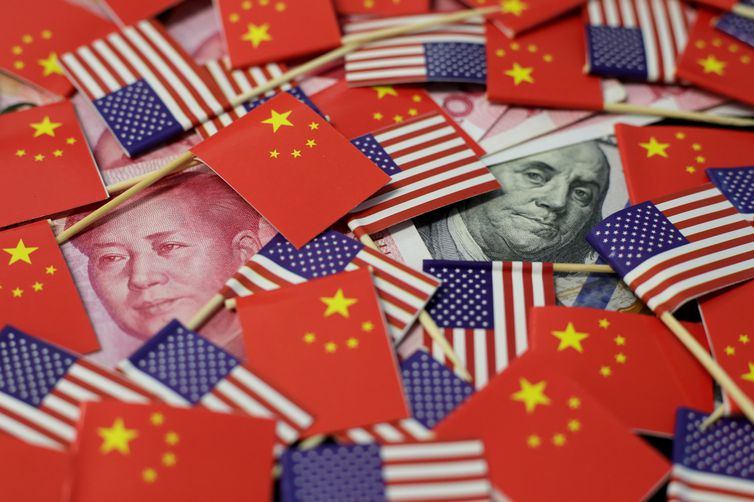 FILE PHOTO: A U.S. dollar banknote featuring American founding father Benjamin Franklin and a China's yuan banknote featuring late Chinese chairman Mao Zedong are seen among U.S. and Chinese flags in this illustration picture taken May 20, 2019.