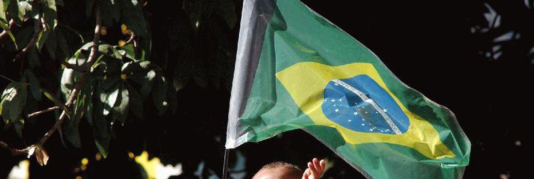 Criança brinca com a bandeira do Brasil