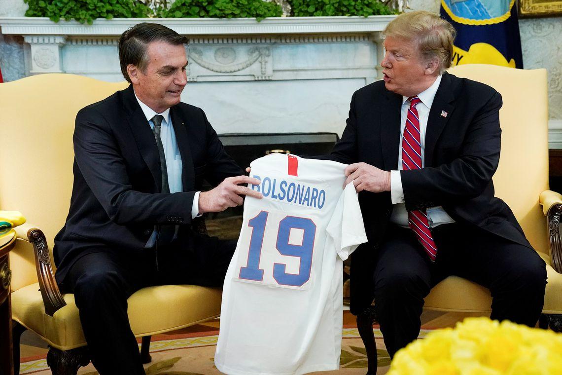 O presidente dos EUA, Donald Trump, dá ao presidente do Brasil, Jair Bolsonaro, uma camisa da seleção de futebol dos EUA durante uma reunião no Salão Oval da Casa Branca , em Washington (EUA).