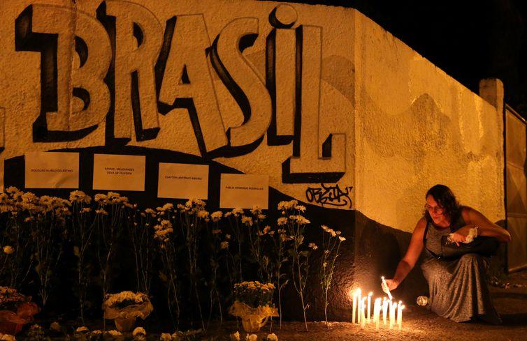 Uma mulher acende velas durante homenagem às vítimas do tiroteio na escola Raul Brasil em Suzano, São Paulo.