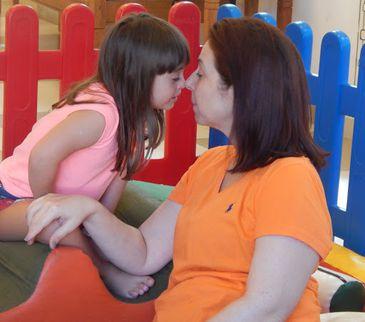 Sentadas em um brinquedo de criança, Maria Daniele e Paola encostam nariz com nariz, de olhos fechados