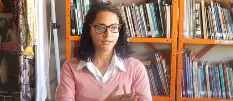 Descrição da foto: Em uma sala, Taís Victa está sentada olhando para frente. Ela usa óculos de grau. No fundo, tem estantes laranjas com livros enfileirados.