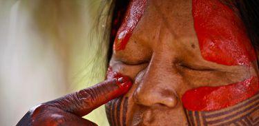 Índio fazendo pintura no rosto