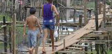 """Em meio à falta de saneamento, moradores equilibram-se em """"ruas"""" de madeira para chegar a suas casas - Altamira, Pará"""