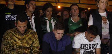 Sobreviventes do acidente aéreo da Chapecoense, Helio Zampier Neto, Alan Ruschel e Jackson Follman, em oração durante homenagem do município de La Unión (Colômbia) a eles e aos familiares das vítimas