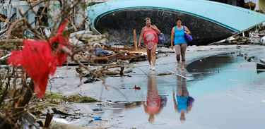 Women walk through the rubble in the aftermath of Hurricane Dorian on the Great Abaco island town of Marsh Harbour, Bahamas, September 3, 2019. REUTERS/Dante Carrer