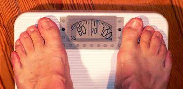 Close dos pés de homem em balança que indica o peso