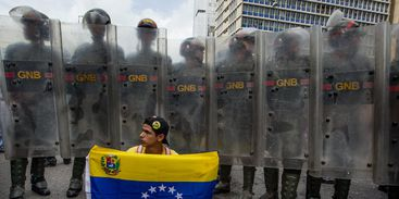 A demonstrator protests with the national Venezuelan flag in front of Riot Police officrs during a rally against Venezuelan President Nicolas Maduro