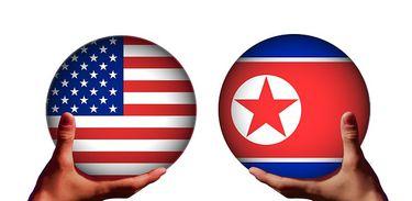 Mãos seguram esferas com desenho das bandeiras da Coréia do Norte e dos Estados Unidos