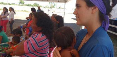 Voluntária com criança venezuelana no Centro de Referência ao Imigrante, em Roraima