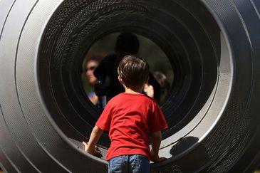 Menino brinca entrando em túnel de parquinho