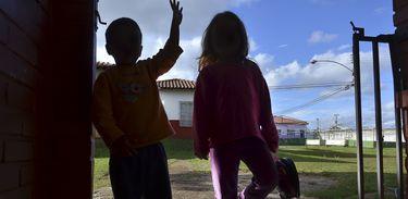 Silhueta a contraluz de duas crianças brincando
