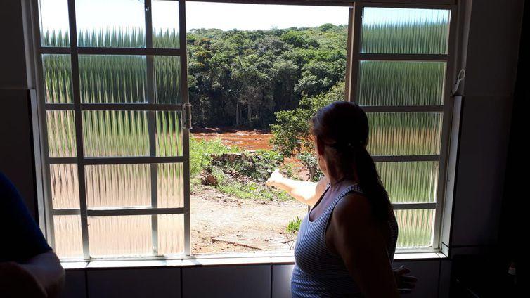 Sandra Maria observa o local tomado pela lama da janela de sua casa em Brumadinho