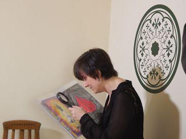 Descrição da foto: Christina Brazil está segurando um livro aberto com uma das mãos. Com a outra mão, ela está segurando uma lupa de aumento e olhando através da lente para figuras coloridas nas páginas do livro.