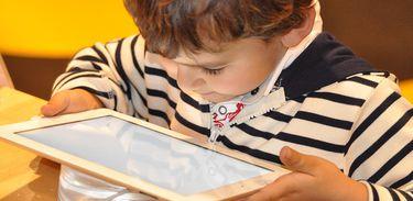 Criança observa tela de um tablet