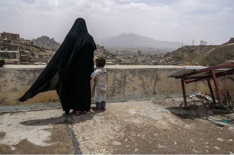 Uma mulher deslocada internamente e sua filha olham a cidade de Sanaa, no Iêmen, a partir do telhado do prédio onde estão abrigadas