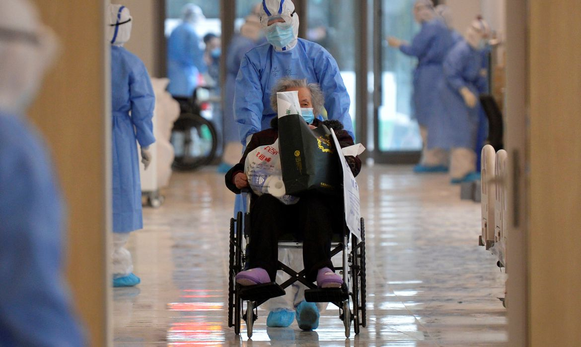 Medical worker in protective suit moves a novel coronavirus patient in a wheelchair at a hospital in Wuhan