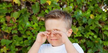Criança coçando os olhos