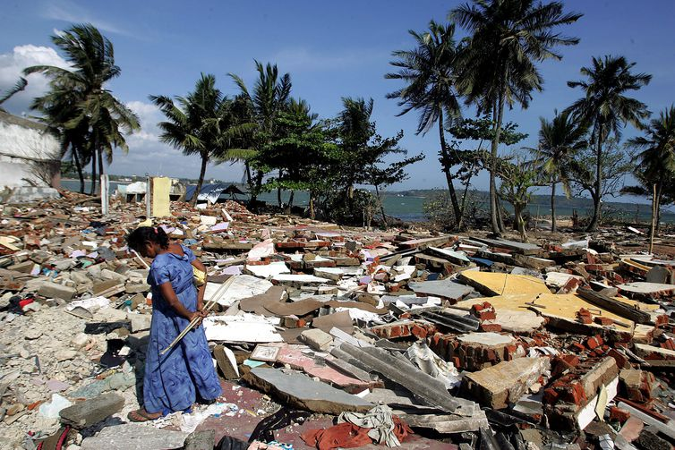 FILE PHOTO: A woman wanders around the rubble in the commercial center of the town of Galle, southern Sri Lanka, on January 30, 2005 after it was flattened by the December 26 tsunami. REUTERS/Desmond Boylan/File Photo FROM THE FILES- 15TH