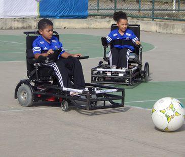 Em uma quadra em espaço aberto, Guilherme está mais à frente, sentado na cadeira de rodas motorizada. Logo atrás, está Lara, também sentada na cadeira de rodas motorizada. À frente da cadeira de Guilherme uma bola de futebol em tamanho maior que o convenc