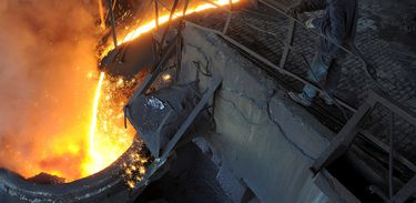 FILE PHOTO: A worker monitors molten iron pouring into a furnace at steel manufacturing plant in Hefei, Anhui province August 15, 2012.   REUTERS/Stringer/File Photo