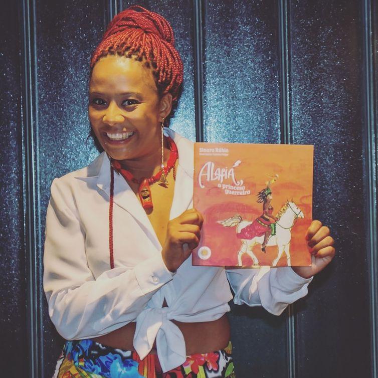 A escritora Sinara Rúbia com o  livro de literatura infanto juvenil contando a história de uma princesa negra.
