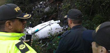 Policiais observam pedaço do avião da Chapecoense destroçado em acidente aéreo