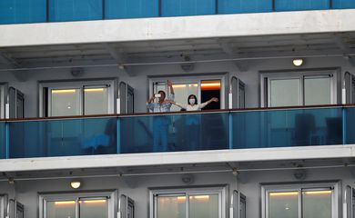 Passengers wave from the cruise ship Diamond Princess in Yokohama