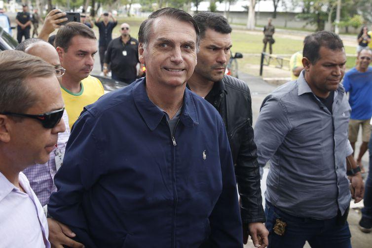 O candidato à Presidência Jair Bolsonaro (PSL) chega à seção eleitoral na Escola Municipal Rosa da Fonseca, na Vila Militar, acompanhado do filho Flávio Bolsonaro, que é candidato ao Senado. Agentes da Polícia Federal e militares do Exército