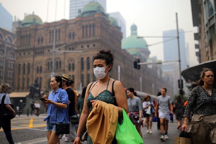 Pedestrians are seen wearing masks as smoke haze from bushfires in New South Wales blankets the CBD in Sydney, Australia, December 10, 2019. AAP Image/Steven Saphore/via REUTERS    ATTENTION EDITORS - THIS IMAGE WAS PROVIDED BY A THIRD PARTY. NO