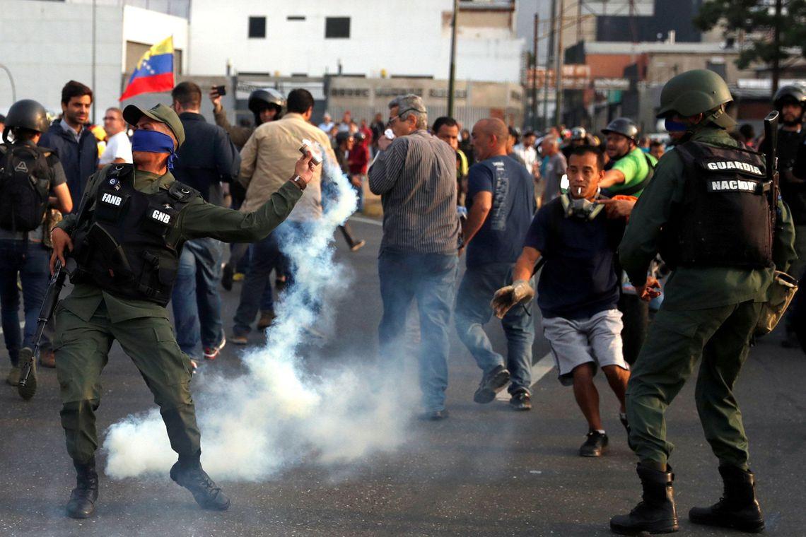 """Um militar lança uma bomba de gás lacrimogêneo perto da Base Aérea """"La Carlota"""", em Caracas, Venezuela."""