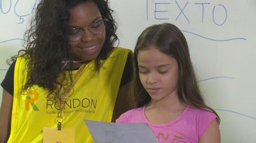 Criança lê texto produzido durante atividade com rondonistas
