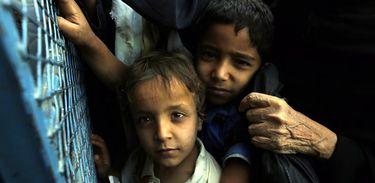 Crianças iemenitas afetadas pelo conflito esperam por um prato de comida doado por uma ação de caridade local. Mais da metade da população do Iêmen passa fome, após dois anos de conflito