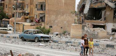 Crianças sírias passeiam entre prédios danificados e ruas cheias de ruínas