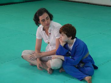 Descrição de foto: Cláudia e Felipe, mãe e filho, estão sentados lado a lado em cima do tatame verde. Ele está vestindo um kimono azul de jiu-jitsu, e está com uma das mãos na perna da mãe, enquanto apoia a cabeça na outra.