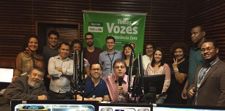 O apresentador Marcus Aurélio (sentado ao centro segurando o microfone) rodeado por diversos integrantes da equipe de profissionais, colaboradores e ouvintes que dinamizam diariamente o Todas as Vozes